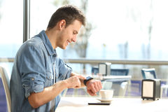 Man using a smartwatch in a coffee shop Stock Photo
