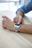 Man using smartwatch connected to smartphone Stock Photo