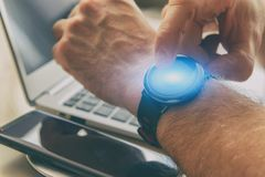 Man using smartwatch in office royalty free stock image