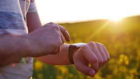 Man using smartwatch on sunset in field of flowers. Man using smart watch on sunset background in a field of flowers. Close-up hands stock footage