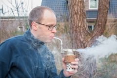 Man using a smoker made for beekeeping. Man produces smoke by blowing into a smoker. Used for beekeeping to subdue the aggressivity of the bees Stock Photography