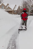 Man Using a Snow Blower. A photo of a man using a snow thrower to clean his driveway of snow royalty free stock photography