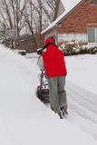 Man Using a Snow Blower. A photo of a man using a snow thrower to clean his driveway of snow Royalty Free Stock Images