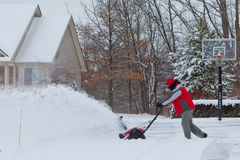Man Using a Snow Blower. A photo of a man using a snow thrower to clean his driveway of snow royalty free stock photo