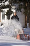 Man Using Snow Blower. On sunny winter day Stock Image