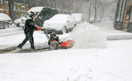 Man using snow blower. New York, February 9, 2017: A man is using a snow blower to clear sidewalk during a heavy snowfall stock images