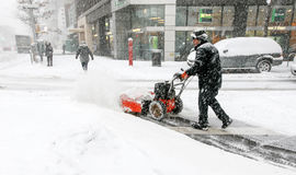 Man using snow blower. New York, February 9, 2017: A man is using a snow blower to clear sidewalk during a heavy snowfall royalty free stock photography