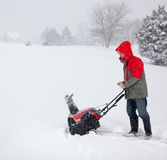 Man using snow blower on snowy drive. Senior man in red coat using a snow blower during a blizzard on home drive stock photography
