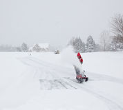 Man using snow blower on snowy drive Royalty Free Stock Photo