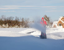 Man using snow blower on snowy drive. Senior man in red coat using a snow blower during a blizzard on home drive royalty free stock images