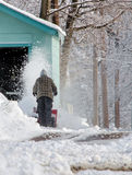 Man using a snow blower. A man uses a snow blower to clear snow from his driveway after a cold, winter in Michigan royalty free stock images