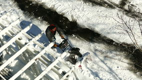 Man using snow plower on the pavement to remove snow stock video footage