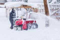Man using snow removal, snow blower, machine. Hokkaido, Japan - 28 December 2017 - Unidentified man use his red snow removal machine to clear path way at public stock photos