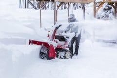 Man using snow removal machine, snow blower. Hokkaido, Japan - 28 December 2017 - Unidentified man use his red snow removal machine, snow blower, to clear path stock image
