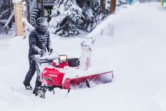 Man using snow removal machine. Hokkaido, Japan - 28 December 2017 - Unidentified man use his red snow removal machine to clear path way at a park in Hokkaido royalty free stock image