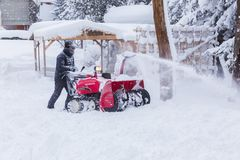 Man using snow removal machine. Hokkaido, Japan - 28 December 2017 - Unidentified man use his red snow removal machine to clear path way at a park in Hokkaido stock photos