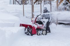 Man using snow removal machine. Hokkaido, Japan - 28 December 2017 - Unidentified man use his red snow removal machine to clear path way at a park in Hokkaido stock photo