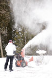 Man Using Snow Thrower. A man clears snow from a driveway after a January storm with a heavy duty gas snow blower royalty free stock image