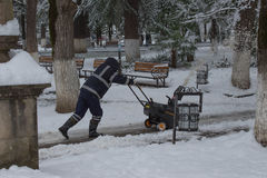 Man using a snow throwing machine on a winter day after a snowstorm dumped 8 inches of snow. Man operating a snow blower. Man removes snow with gas snow royalty free stock photos