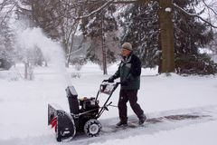 Snowblower Man Blowing Snow Away From Viewer. A man using a snowblower during a blizzard royalty free stock photos