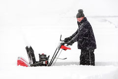 Man using a snowblower. A man snow blowing his driveway stock image
