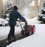 Man Using Snow Blower. A man uses a snow blower to remove snow from a driveway during a winter storm stock photography
