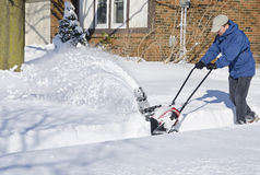 Man Using Snowblower to Clear Snow #2. Man removing snow with a snow blower #2 royalty free stock image