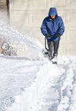 Man Using Snowblower to Clear Snow. Man removing snow with a snow blower royalty free stock photography
