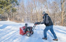 Man using Snowblower. Man uses a snowblower to clear snow from his driveway royalty free stock image