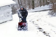 Man using Snowblower. Man uses a snowblower to clear snow from his driveway Stock Images
