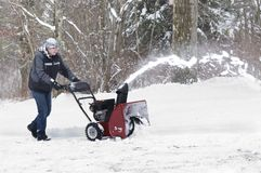 Man using Snowblower. Man uses a snowblower to clear snow from his driveway Royalty Free Stock Photography