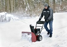 Man using Snowblower. Man uses a snowblower to clear snow from his driveway Royalty Free Stock Images