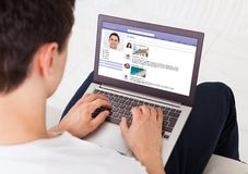 Man using social networking site on laptop at home Stock Photography