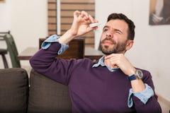 Man using some eye drops at home Stock Photos