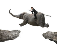 Man with using speaker riding elephant flying over two cliffs Royalty Free Stock Images