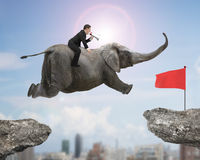 Man with using speaker riding elephant flying toward red flag Stock Photo