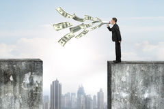 Man using speaker yelling with dollar bills spraying out. Man using megaphone yelling with dollar bills spraying out, on top of high concrete wall royalty free stock images