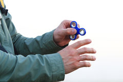 Man using spinner outdoors. Man`s hand with fidget on white background stock photo