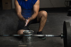 Man using sports chalk in a gym. Closeup of a strong man using some gym chalk on his hands before lifting a barbell Royalty Free Stock Photography