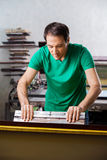 Man Using Squeegee In Paper Factory Royalty Free Stock Photography