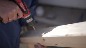 Man using a steel drill and usual screwdriver on wooden plate stock footage