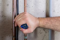 Man using strength to turn a water valve on a pipe. Gripping it with his hand indoors in a utility room in a close up view Royalty Free Stock Image