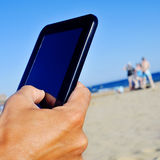 Man using a tablet on the beach Stock Photo
