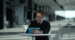 Man using tablet in cafe. Mature man sitting in cafe of modern office building and using tablet stock video footage