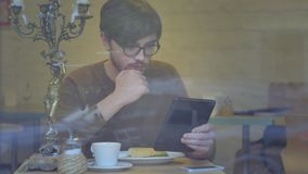 Man Using a Tablet in the Cafe. A young boy sipping coffee and looking at the tablet stock video footage