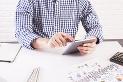 Man using tablet. Man in casual shirt using tablet at office desk with business sketch and calculator on white brick background Royalty Free Stock Photos