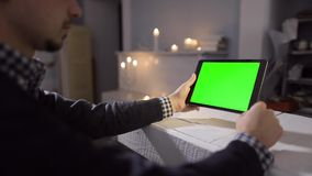 Man Using Tablet in Coffee Shop. Tablet with Green Screen. So you can easily crop and zoom, Great for presentation and. Using Smart Phone on Wood Table wvarious stock video footage