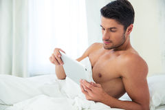 Man using tablet computer in the bed Royalty Free Stock Photography