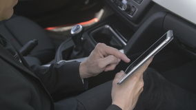Man using a tablet computer. Caucasian man using a tablet computer in the passenger seat in a car. For concepts such as sms, text messaging, chat and web stock video footage