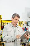 Man Using Tablet Computer In Hardware Store Royalty Free Stock Image